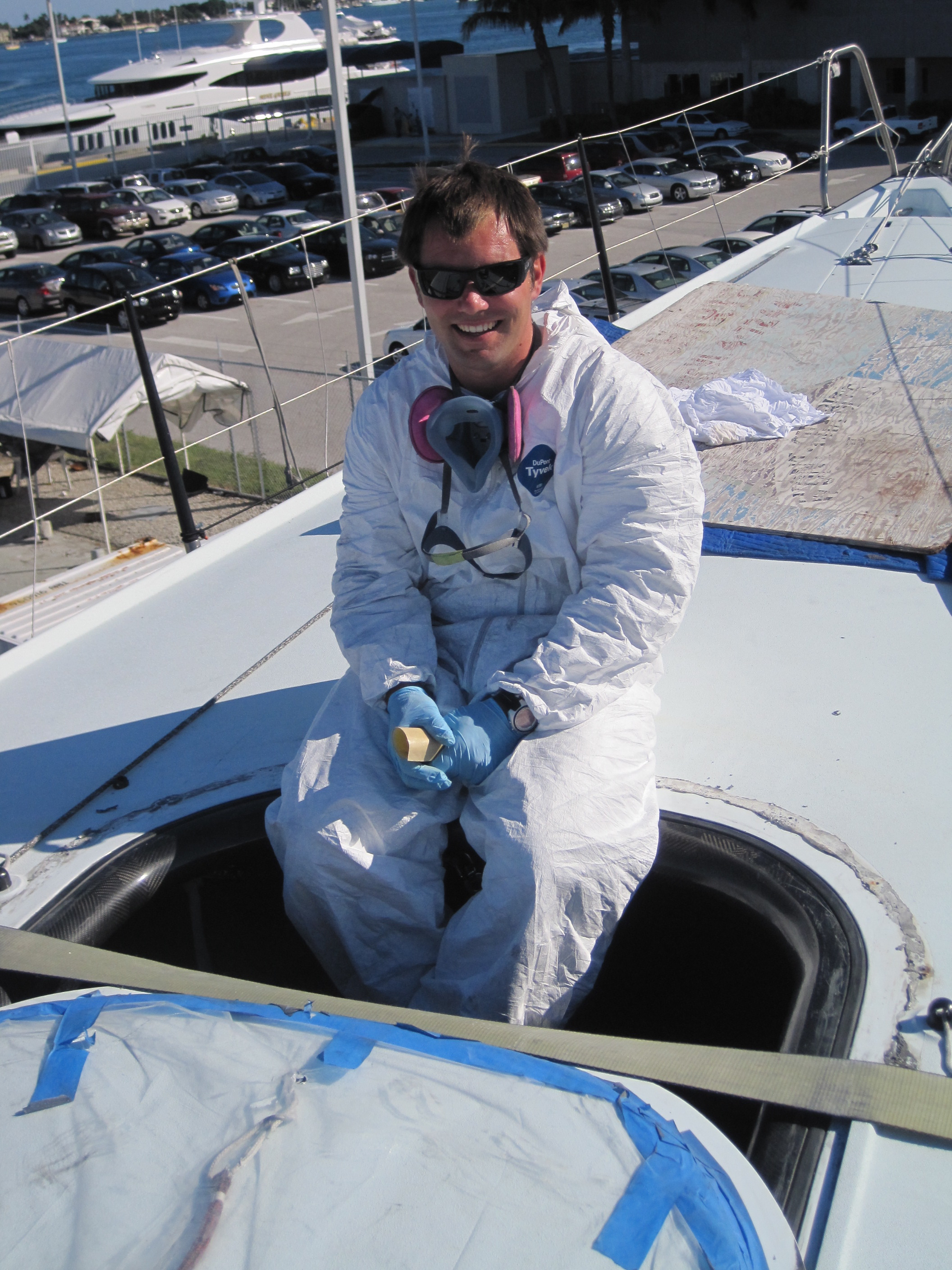 Thomas Allin smiles despite working through the heat in a Tyvek suit on a leaking hatch cover.